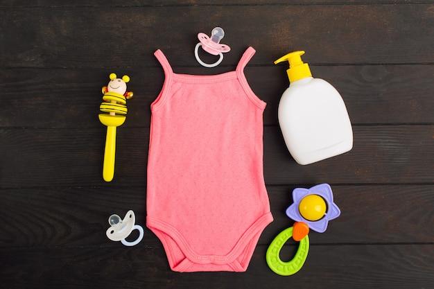 Acessórios para bebê - bodysuit rosa, sabão, chupeta e chocalho sobre a mesa de madeira