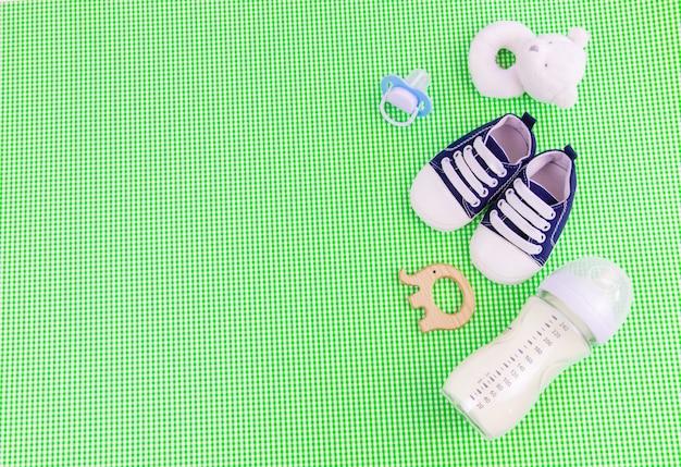 Acessórios para bebês e comida em um fundo verde. foco seletivo. bebê