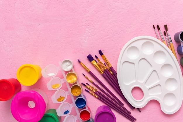 Acessórios para desenhar com tintas em uma superfície rosa