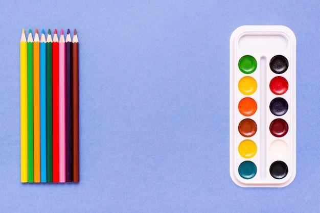 Acessórios para desenhar lápis de cor e aquarela azul conceito lápis contra aquarelas