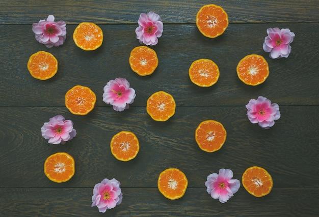 Acessórios para exibição de topo festival de ano novo chinês.orange fatiado e linda flor de ameixa rosa sobre fundo de mesa de madeira.