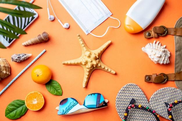 Acessórios para férias na praia ao redor de uma estrela do mar em fundo laranja