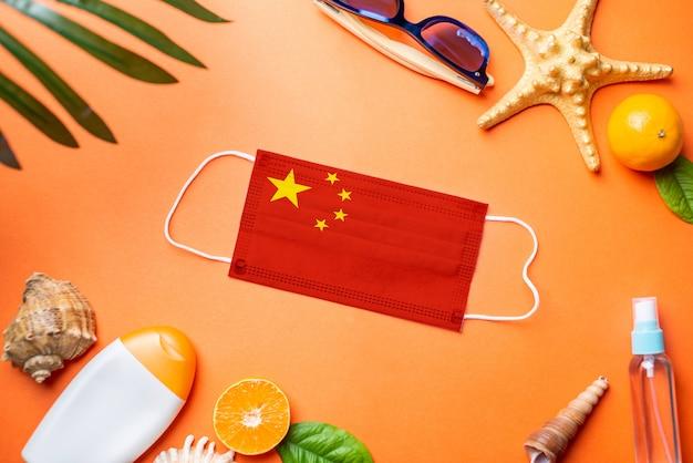 Acessórios para férias na praia em torno de uma máscara protetora com a bandeira da china