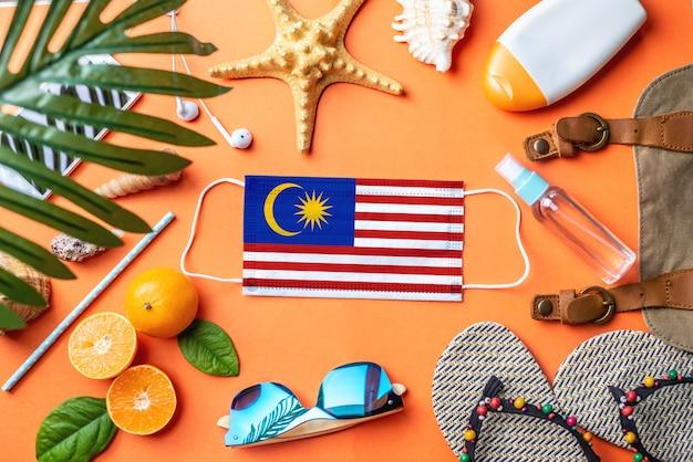 Acessórios para férias na praia em torno de uma máscara protetora com a bandeira da malásia