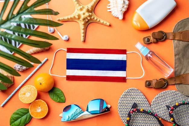 Acessórios para férias na praia em torno de uma máscara protetora com a bandeira da tailândia