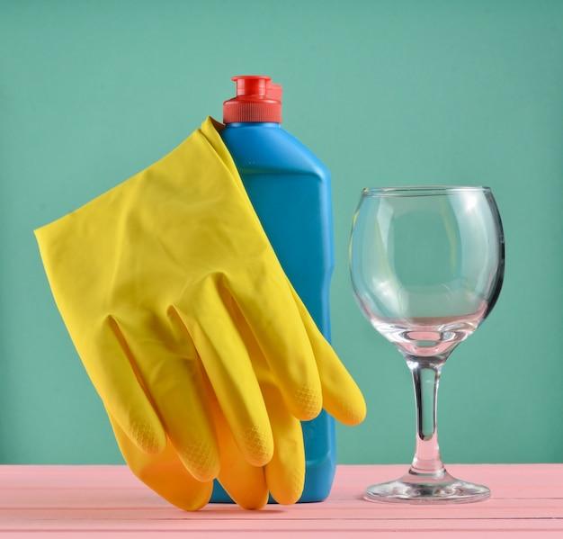 Acessórios para lavar louça e limpeza de casas. lavar pratos. frasco de detergente, vidro e luvas de borracha amarela