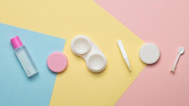 Acessórios para lentes de contato em um fundo multicolorido. a vista do topo.