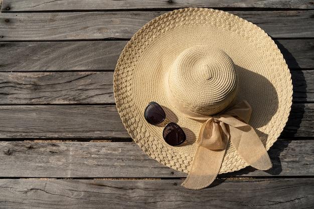 Acessórios para o feriado, óculos de sol e chapéu de mar na ponte de madeira