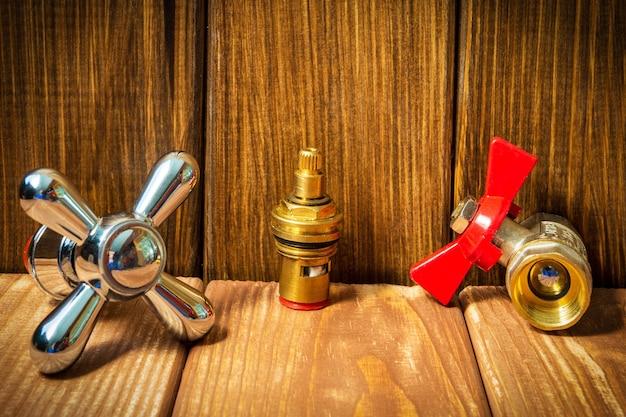 Acessórios para reparos de encanamento ou lavagem na cozinha em um fundo vintage de madeira.