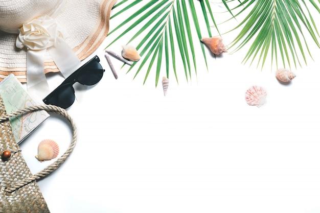 Acessórios para viajantes, galhos de folhas de palmeira tropical e chapéu grande isolado