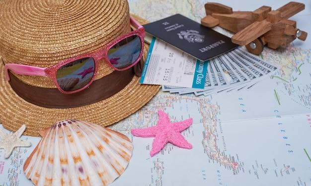 Acessórios para viajantes planos leigos com folha de palmeira, câmera, chapéu, passaportes, dinheiro, passagens aéreas, aviões, mapa e óculos de sol. vista superior, conceito de viagens ou férias.