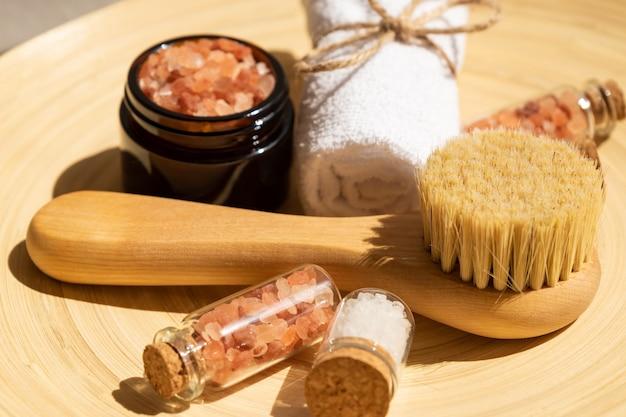 Acessórios pessoais de tratamento de spa com pbush facial, sal rosa aromático e toalha branca enrolada. riutina de cuidados com a pele.