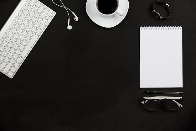 Acessórios pessoais; xícara de café; fone de ouvido; óculos e teclado em fundo preto