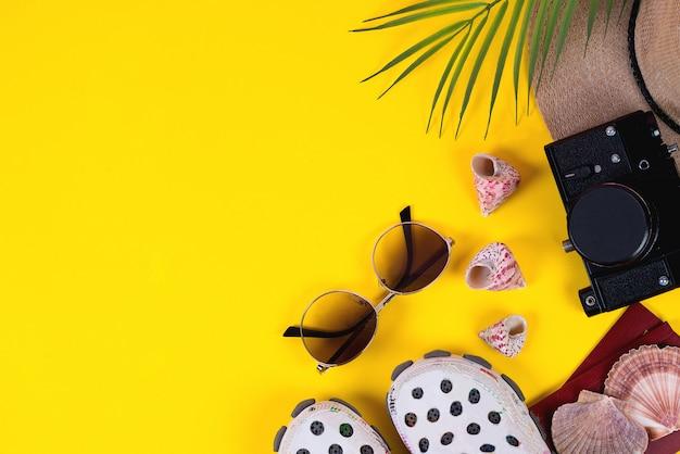 Acessórios planos para viajantes em um fundo colorido com um chapéu de palha, câmera e óculos de sol. copie o espaço