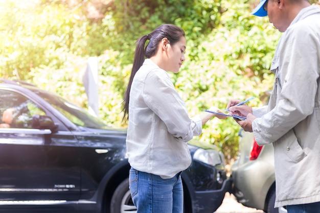 Acidente de carro acidente de carro mulher conversando com um agente de seguros sobre o acidente. agente de seguros