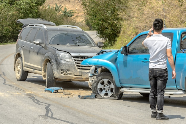 Acidente de carro de acidente de carro na estrada rural entre saloon versus pickup espera seguro.