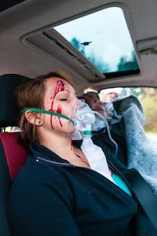 Acidente de carro - vítima em veículo acidentado recebendo primeiros socorros