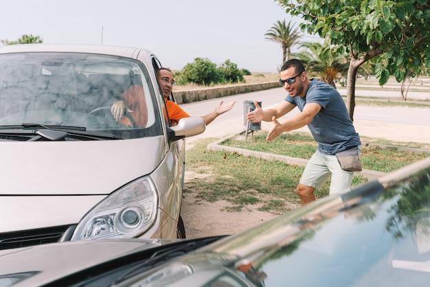 Acidente entre dois carros com 2 pessoas ao ar livre