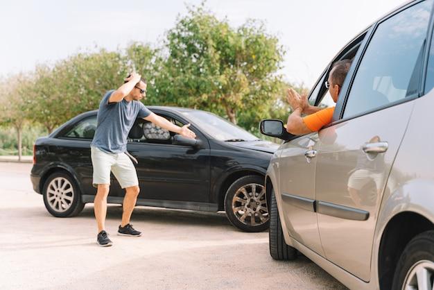 Acidente entre dois carros com duas pessoas ao ar livre