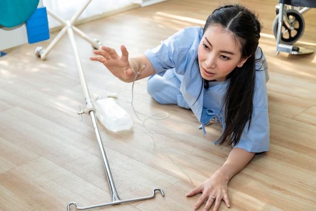 Acidente paciente linda mulher asiática caindo e rastejando por ajuda no quarto do hospital.