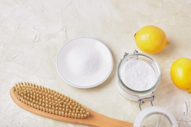 Ácido cítrico, refrigerante, limão e uma escova de madeira em um fundo claro