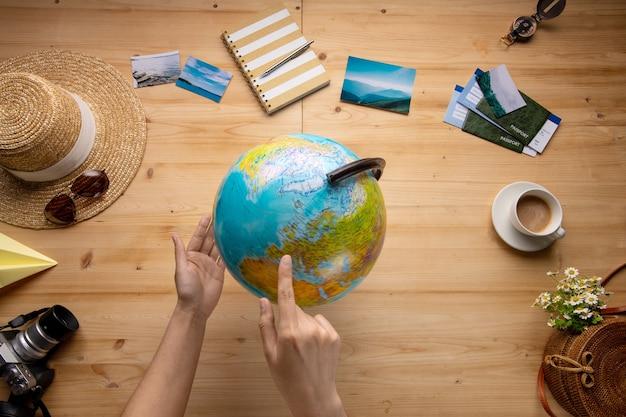 Acima, a imagem de uma mulher apontando para o globo enquanto escolhe o país para viajar