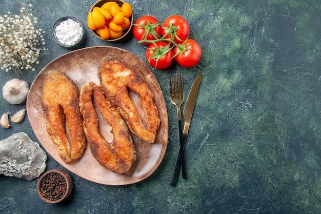 Acima, a vista de um delicioso peixe frito em um prato marrom e talheres define alimentos com especiarias em uma mesa de mistura de cores com espaço livre
