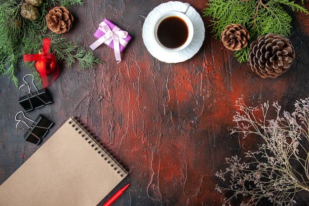 Acima, a vista do abeto ramifica uma xícara de acessórios de decoração de chá preto e um presente ao lado do caderno com uma caneta na mesa escura