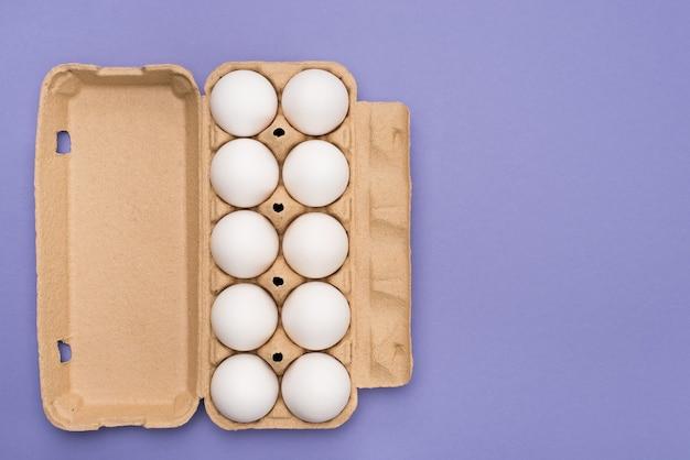 Acima acima da cabeça, close-up, vista da foto do recipiente de papelão com dez ovos brancos isolados de fundo de cor roxa com espaço de cópia