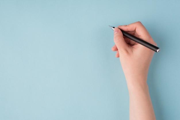 Acima acima da cabeça, feche a foto da visão em primeira pessoa da mão direita de uma garota segurando uma caneta preta e começando a escrever isolada sobre um fundo azul pastel