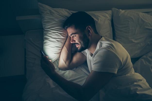 Acima, acima, retrato de alto ângulo dele, ele é um cara atraente, alegre e alegre, deitado na cama, usando celular digital, conversando à noite, tarde da noite, casa, quarto escuro iluminado, casa plana