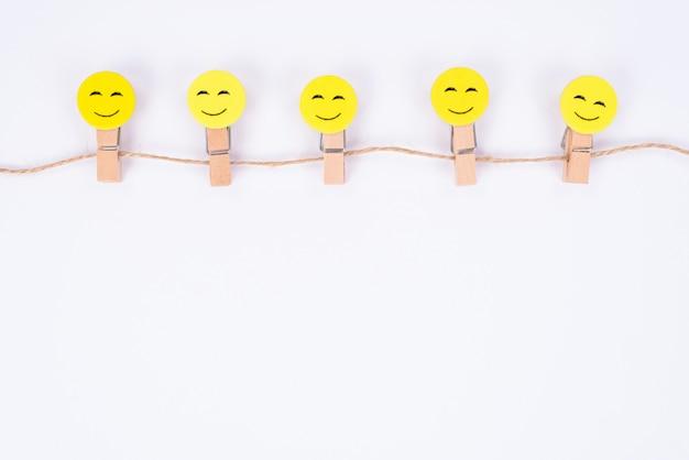Acima, ângulo alto, vista de perto de cinco rostos sorridentes alegres pendurados em uma parede branca isolada de barbante