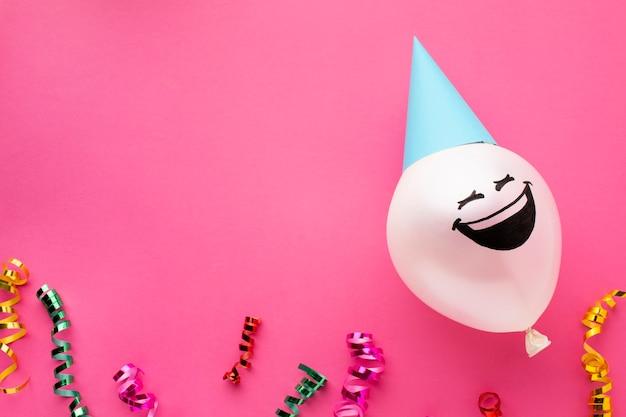 Acima da moldura com balão e chapéu de festa