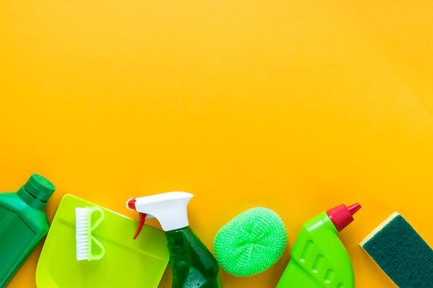 Acima da moldura da vista com produtos de limpeza em fundo amarelo