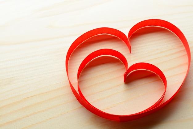 Acima de duas fitas vermelhas em forma de coração com fundo de madeira.