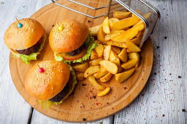 Acima de hambúrguer com batatas fritas e cesta de fritura na placa de alimentos