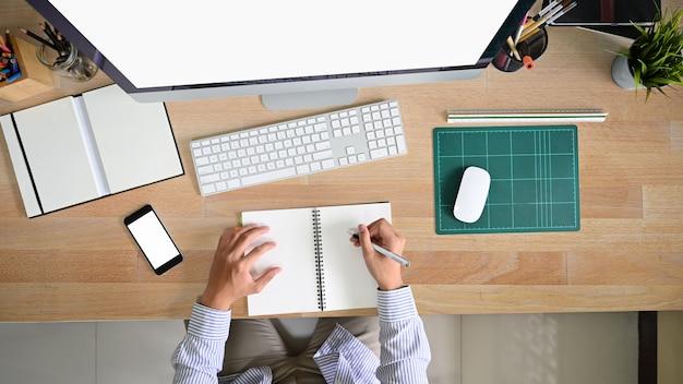 Acima de headshot jovem trabalhando no espaço de trabalho de escritório com mesa de madeira.