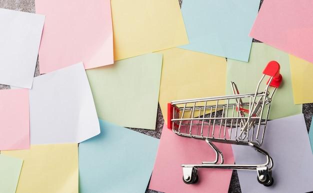 Acima de muitos papel em branco, lista de notas com o carrinho de compras