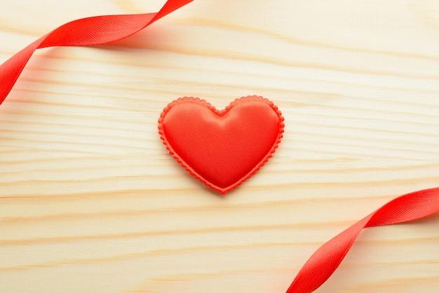Acima de um pequeno coração de tecido e fitas em fundo de madeira.