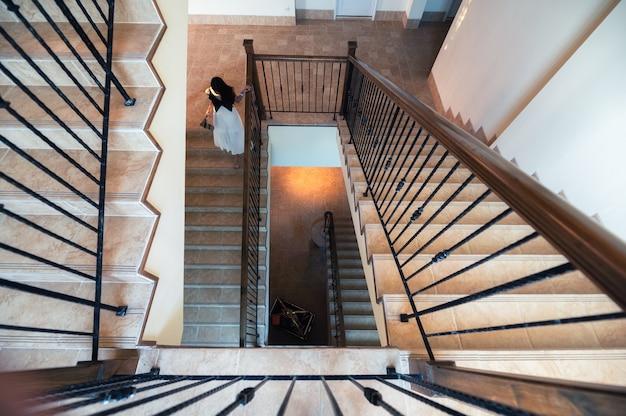 Acima de uma escada antiga com uma mulher de vestido caminhando no hotel