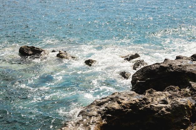 Acima de ver a água ondulada na costa rochosa