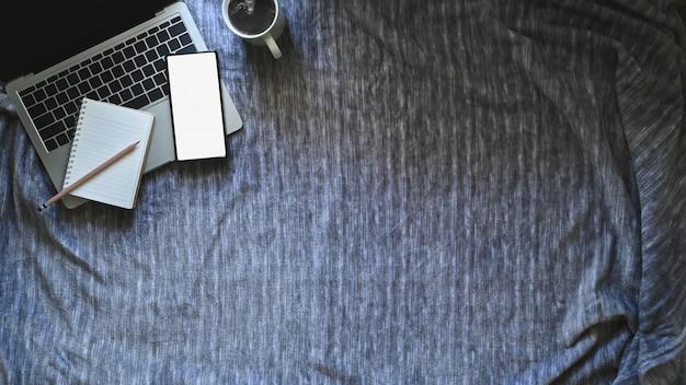 Acima do computador portátil, caderno e lápis, café com maquete smartphone na cama cobertor.