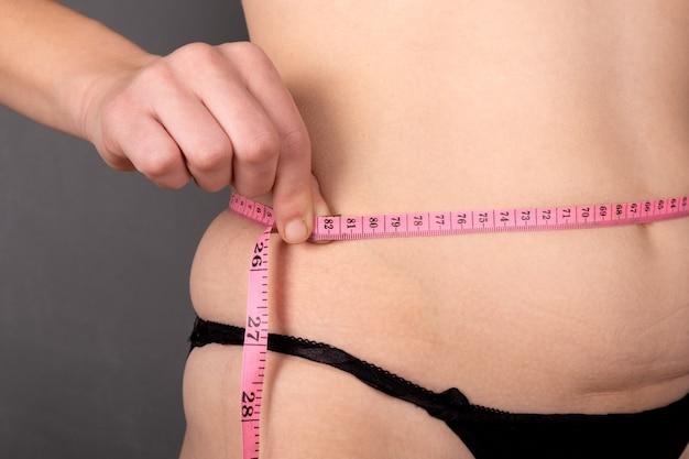 Acima do peso, uma menina mede a cintura com um centímetro. Foto Premium