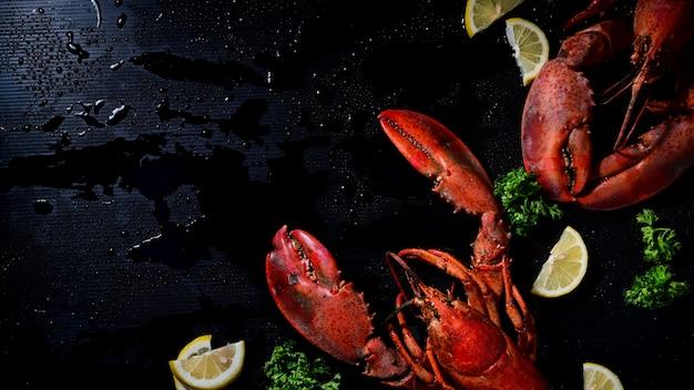 Acima do tiro dois lagosta com limão e salsa, fundo escuro de copyspace.