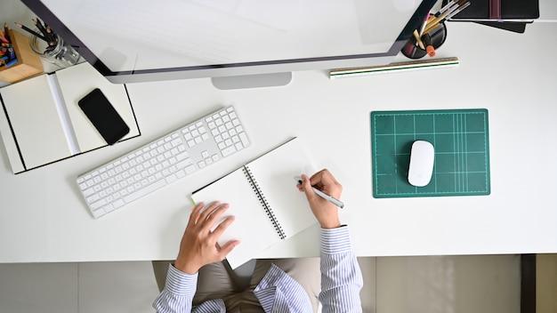 Acima do tiro, homem escrevendo o caderno na mesa do espaço de trabalho do escritório moderno.
