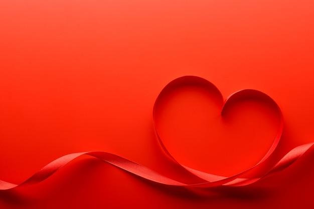 Acima, fitas vermelhas em formato de coração na mesa