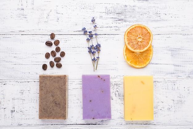 Acima, foto de visão aérea de barras de sabonete orgânico artesanal com grãos de café lavanda e fatias de laranja secas isoladas em fundo branco de madeira