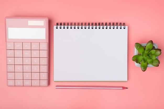 Acima, foto de visão aérea de um caderno, uma calculadora feminina e uma suculenta isolada em um fundo rosa pastel com um copyspace em branco vazio