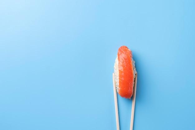 Acima, pauzinhos segurando sushi