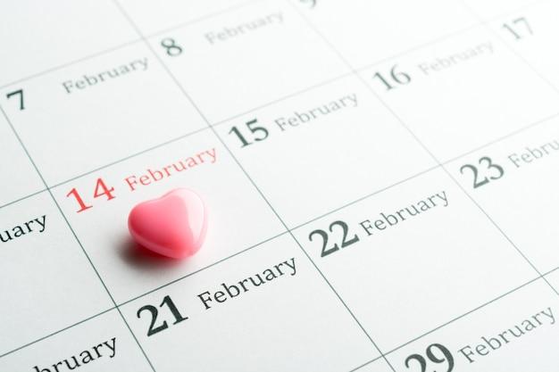 Acima, pequeno coração rosa em 14 de fevereiro - dia de são valentim na página do calendário.